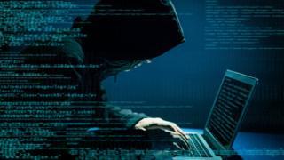 Un hombre en la sombra con pinta maliciosa entrando en un computador.