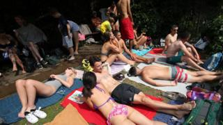 People sunbathing at the mixed bathing pond on Hampstead Heath, London