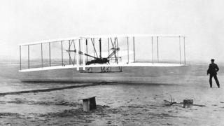 The Wright Flyer as his brother Wilbur Wright looks on when the plane made its s first flight at Kitty Hawk, North Carolina, Dec. 17, 1903.