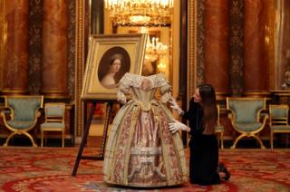 A Buckingham Palace staff member poses with Queen Victoria's Stuart Ball costume at the press preview of Queen Victoria's Palace which goes on public display from July 20 at the Summer Opening of the State Rooms at Buckingham Palace in London, Britain, 2 April 2019.