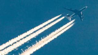 A passenger aircraft and its engine exhaust contrails