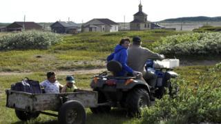 Children ride in a trailer in the village of Chavanga, in Russia's Arctic Murmansk region.