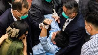A pro-democrat lawmaker is restrained by security guards at the Legislative Council in Hong Kong