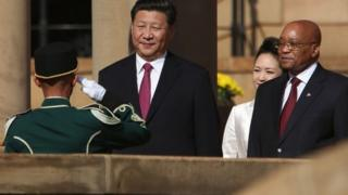 Chinese President Xi Jinping (L) stands in front of the Guard of Honour, flanked by South African President Jacob Zuma (R) at the Union Buildings in Pretoria, during the start of his official tour to South Africa on 2 December 2015
