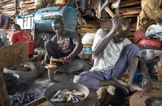 "Blacksmiths are seen at work preparing parts to be used to build boats at the port of Mopti on October 13, 2018. - Due to the strategic position close to the Niger River, fishing represents one of the Mopti""s most important activity"