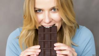 Woman tucks into large chocolate bar