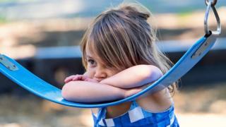 A lonely little girl in a swing