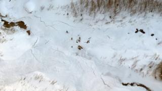 A distant group of rescue workers on skis can be seen in this top-down shot taken by helicopter