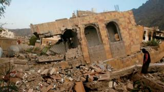 A man walks over the remains of a building destroyed by fighting in Taiz, Yemen (20 November 2016)