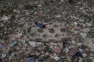 A boy lies on a mattress amongst rubbish