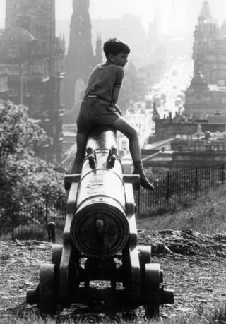Boy sat on top of a cannon on Calton Hill, 1966.
