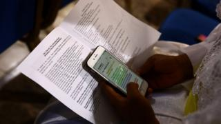 A worshipper reads a passage from the Bible on her smartphone during a Sunday service