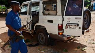 A Burundian policeman stands next to the shrapnel-riddled vehicle in which Tutsi General and security advisor to Burundi's vice president Athanase Kararuza was killed on April 25, 2016 in Bujumbura