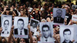 Pessoas seguram fotos de vítimas da ditadura militar em protesto contra a comemoração dos 55 do golpe militar, em SP