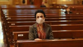 אישה יושבת בכנסייה בלבנון