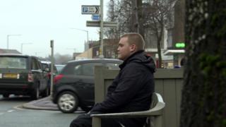 Sam, 23, sitting on bench