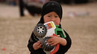Criançasegura carrinho de brinquedo em campo de refugiados de Al-Hol, na Síria