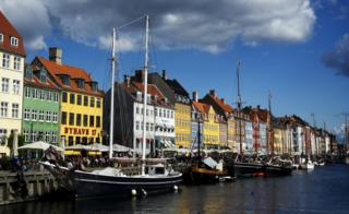 A canal in Copenhagen lined with attractive multi-coloured buildings