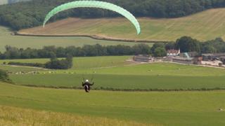 A hang glider lands