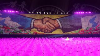 """A mural of shaking hands is displayed during a """"mass games"""" gymnastic and artistic performance at the May Day Stadium in Pyongyang"""