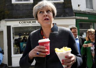 Theresa May holding a hot drink and some chips