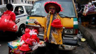 A woman sells Christmas items in front of a vehicle parked along a road in the central business district, near Marina in Lagos, Nigeria December 13, 2016