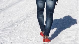 Un migrant de Côte d'Ivoire marche dans la neige avec des baskets et pas de chaussettes en route vers le Col de l'Echelle, un col enneigé pour franchir la frontière entre l'Italie et la France, le 13 janvier 2018 près de Bardonecchia , Alpes italiennes.
