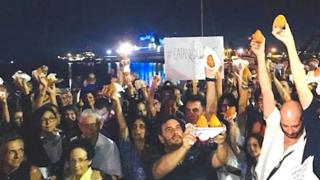 Protestors brandishing arancini in Catania, Sicily, where a boat with around 200 rescued migrants who have been denied permission to disembark