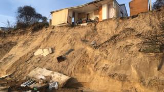 Partially-collapsed house at Hemsby, with debris strewn beneath