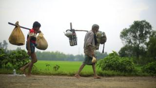 Two generations of a Rohingya refugee family walk with their belongings attached to long sticks across their shoulders