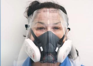 Jodie Bond, a community nurse in unplanned care at Norfolk Community Health and Care NHS Trust, wearing a face shield and respirator