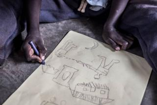 Richard, a young refugee from South Sudan, draws a picture of a violent scene