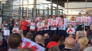 The athletes are applauded on the steps of the Senedd