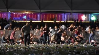 People run from the Route 91 Country Music Festival in Las Vegas after shooting begins
