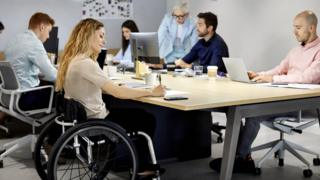Wheelchair using young woman takes notes in a meeting