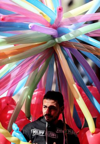 Man under an 'umbrella' of balloons