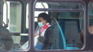 A passenger wearing a protective face mask on a bus in central London, following the announcement that wearing a face covering will be mandatory for passengers on public transport in England