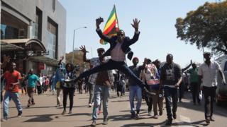 Supporters of the opposition Movement for Democratic Change party (MDC) of Nelson Chamisa, sing and dance as they march in the streets of Harare, 1 August 2018
