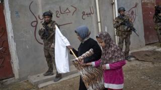 Civilians carry a white flag as they pass by Iraqi special forces on patrol, 2 November 2016