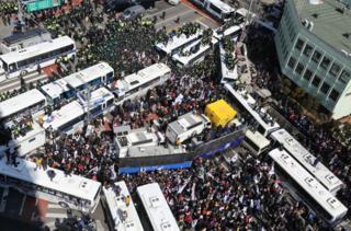 朴槿惠的支持者在朴被弹劾后试图冲过警方的巴士防线,朝宪法法院方向进发。