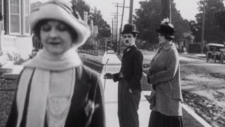 Charlie Chaplin watches as a woman passes by. Beside Chaplin, what we assume to be his wife looks angrily at him. It is visually very similar to the distracted boyfriend meme that was popular in 2017.