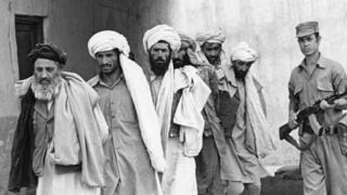 Советский солдат ведет пленных моджахедов