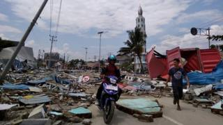 Residents on a street full of debris after an earthquake and tsunami hit Palu, on Indonesia's Sulawesi island.