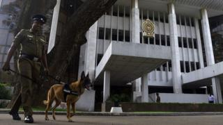 A Sri Lankan policeman walks with a sniffer dog to inspect outside the Sri Lankan Supreme Court in Colombo on December 12, 2018
