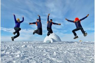 Justin Rowlatt (right) jumping with colleagues and a scientist in Antarctica