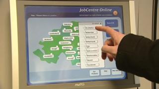 Jobseeker using touch screen machine in JobCentre
