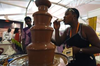 A woman tastes chocolate from a fountain in Abidjan, Ivory Coast - Saturday 1 October 2016