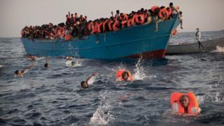 泳いで救助船に乗り込もうとする人々