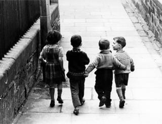 Four children walking down a street, 1966.