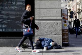 A woman walks by a homeless person who is wearing a face mask